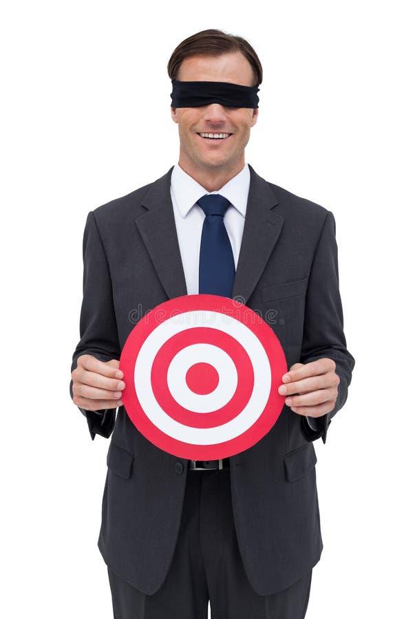 Blindfolded και χαμογελώντας επιχειρηματίας που κρατούν έναν κόκκινο στόχο στοκ εικόνα με δικαίωμα ελεύθερης χρήσης
