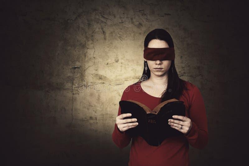 Blindfolded Bible reading stock photo