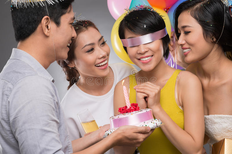 Blindfolded birthday girl. Receiving a cake from her friends stock photos
