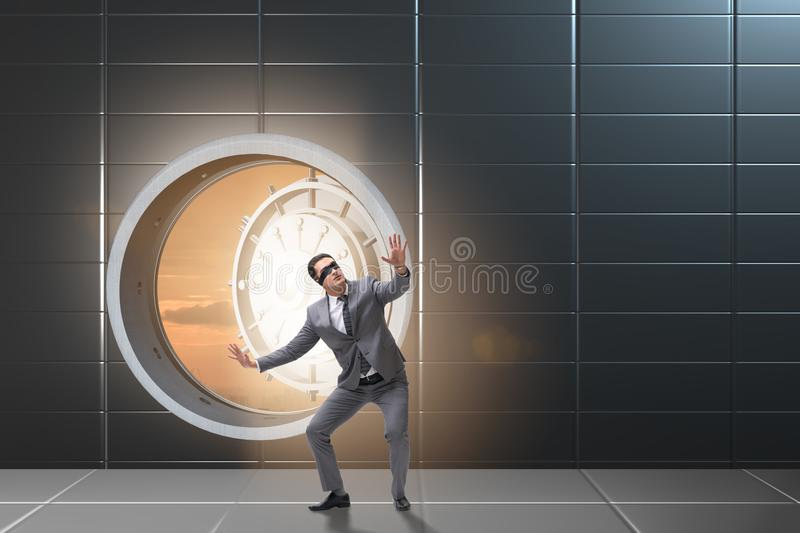 The blindfolded businessman in front ot vault door royalty free stock photos