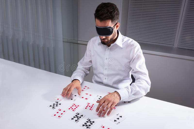 Blindfolded Businessman Reading Cards In Office. Blindfolded Businessman Reading Cards On White Desk royalty free stock image