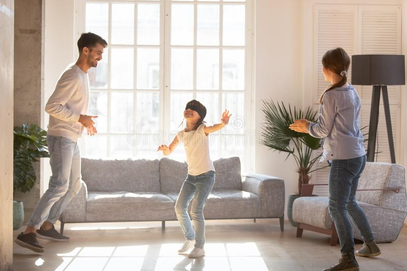 Blindfolded girl catching parents playing hide and seek game. Blindfolded girl catching mother and father playing together hide and seek in living room royalty free stock image
