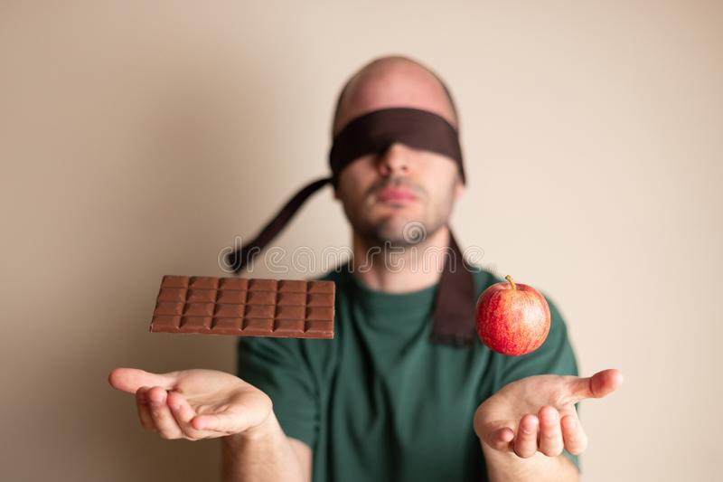 Blindfolded man places hands underneath a chocolate bar and an apple stock images