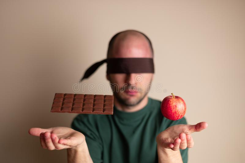 Blindfolded man places hands underneath a chocolate bar and an apple royalty free stock photography