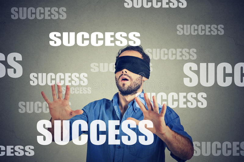 Blindfolded young business man looking for success. Blindfolded business man looking for success stock image