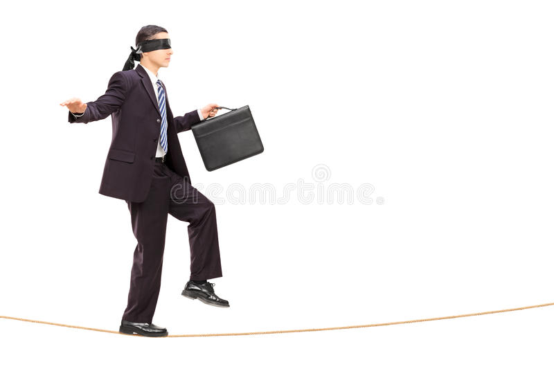 Blindfolded young businessman walking on rope royalty free stock photo