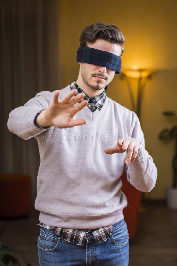 Blindfolded young man at home in living room cannot see royalty free stock images