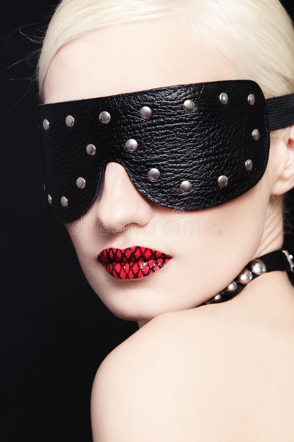 Blindness. Portrait of young beautiful woman in studded blindfold royalty free stock photo