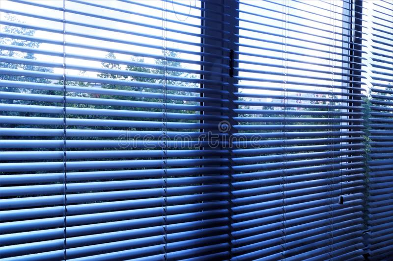Blinds—effective light-shielding device of the horizontal slats. The slats on the Windows are stationary and swivel, regulate. Light and air flow. Blinds stock photo