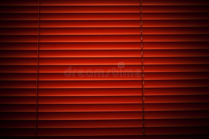 Blinds. Window with rolling shutters system on red tones stock photography