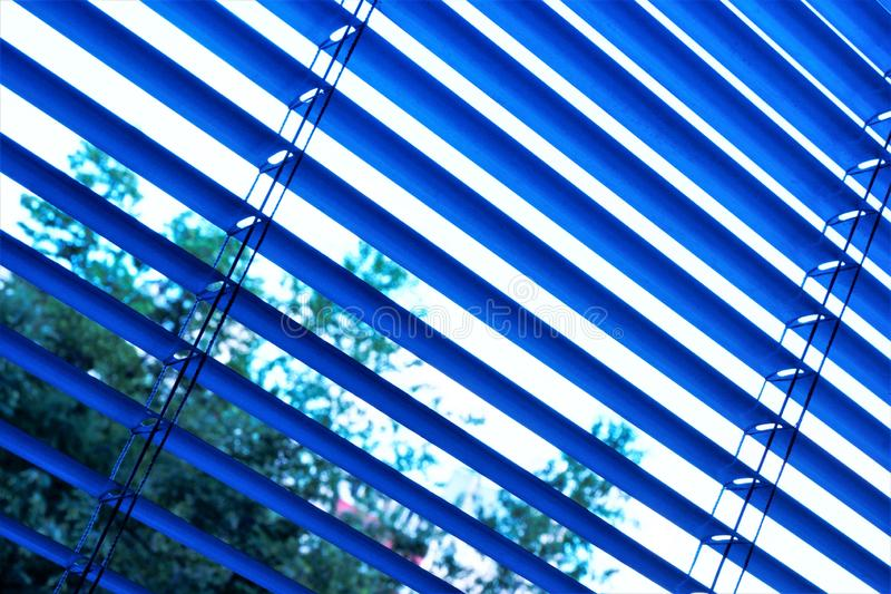Blinds are effective light protection devices made of vertical or horizontal slats. Slats can be fixed or rotated to regulate. Light and air flow. Blinds are royalty free stock images