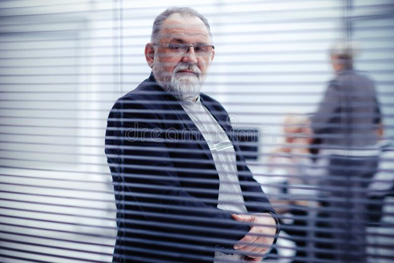 Through the blinds. elderly confident businessman standing in front of office window. stock images