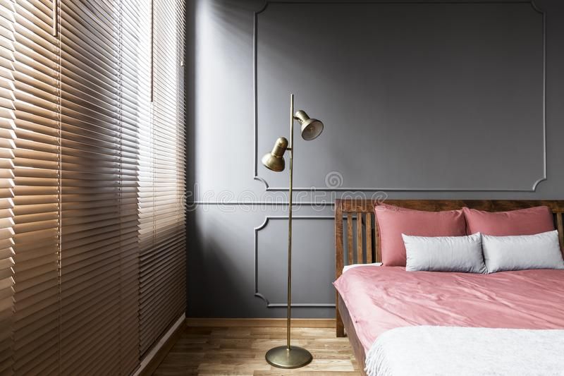 Blinds and golden lamp in dark and elegant bedroom interior with. Pink sheets on a wooden bed and molding on the wall. Real photo royalty free stock photography