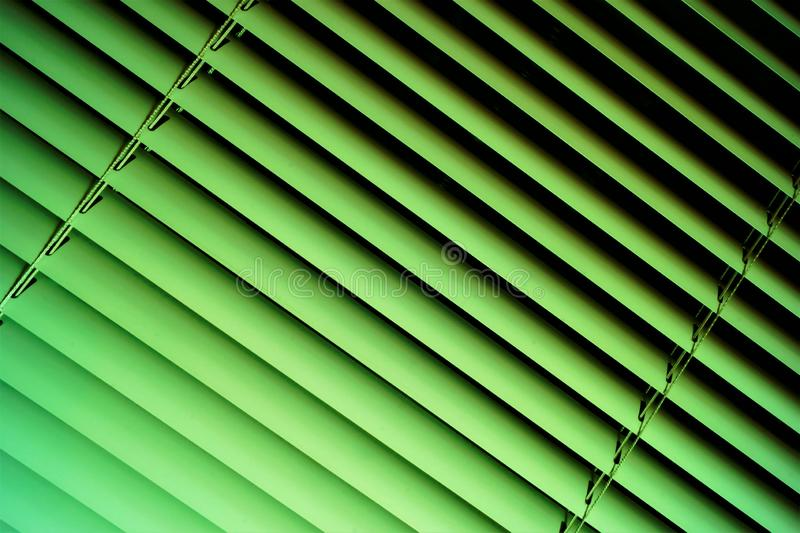 Blinds green background—effective light protection devices from horizontal slats. The slats are stationary or rotated, regulate. Light and air flow royalty free stock photos
