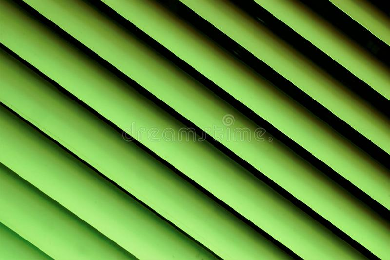 Blinds green background—effective light protection devices from horizontal slats. The slats are stationary or rotated, regulate. Light and air flow royalty free stock images