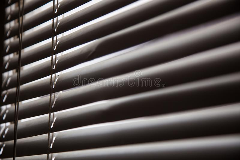 Blinds in a home catching the sunlight,metal shutter window back royalty free stock image