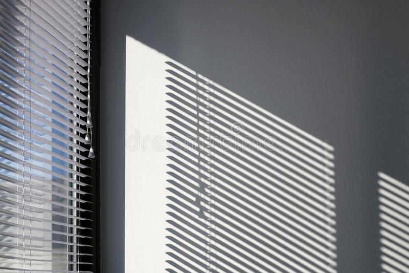 Blinds. Sunlight and blinds creating shadow on a white wall, generic architectural detail stock photos