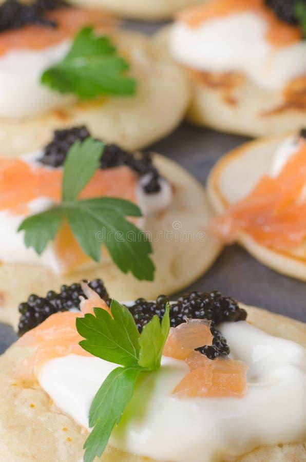 Blini com caviar e salmão fumado fotografia de stock royalty free