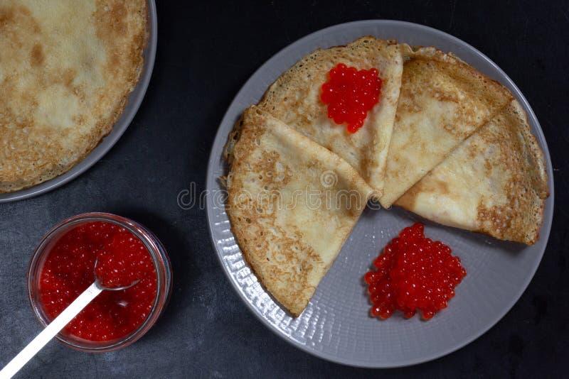 Blini driehoeken of crèmes met rode kaviaar op het bord met pot royalty-vrije stock foto's