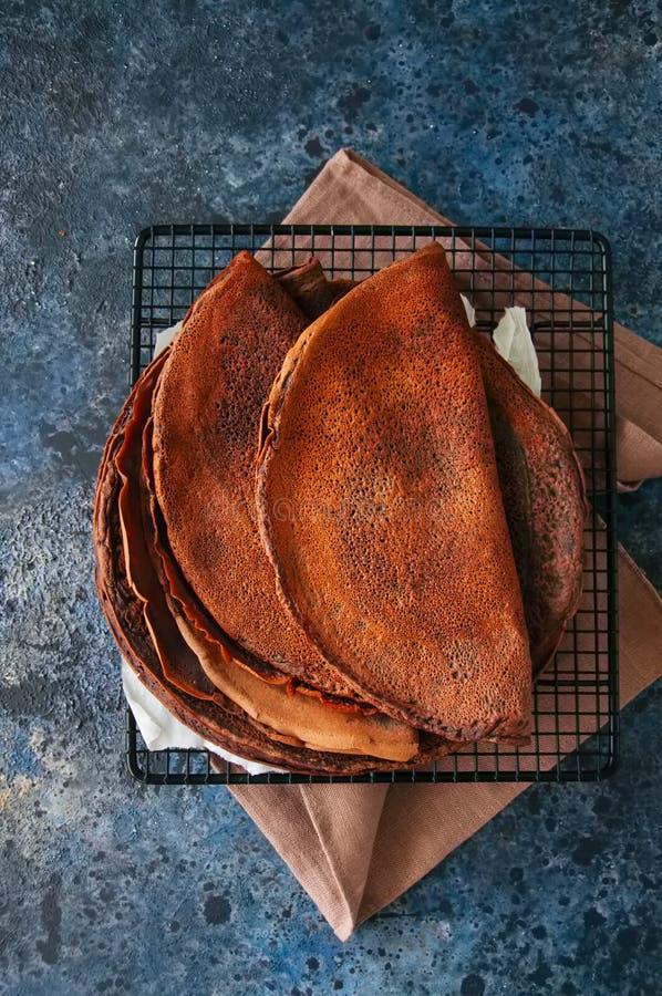 Blinis dos crepes do chocolate em um racke do fio Fundo da pedra azul imagens de stock