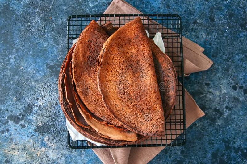 Blinis dos crepes do chocolate em uma cremalheira de fio Fundo da pedra azul foto de stock