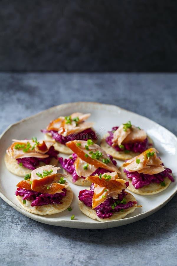 Blinis z śmietankowymi beetroot, koźlim serem i gorącym uwędzonym łososiem, fotografia royalty free