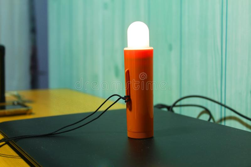 Blinking rescue light of the vessel. Orange blinking life jacket light for seafarer used for unexpected emergency rescue royalty free stock photo