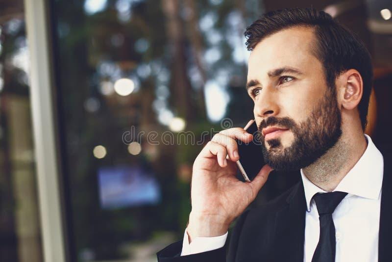 Blisko brodatego młodego mężczyzny wyglądającego spokojnie, rozmawiając przez telefon fotografia royalty free