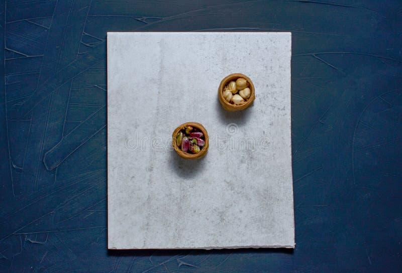 Bliskowschodni deser z pistacją dzwonił mabroume lub Burma odizolowywającymi na błękitnym tle obrazy royalty free
