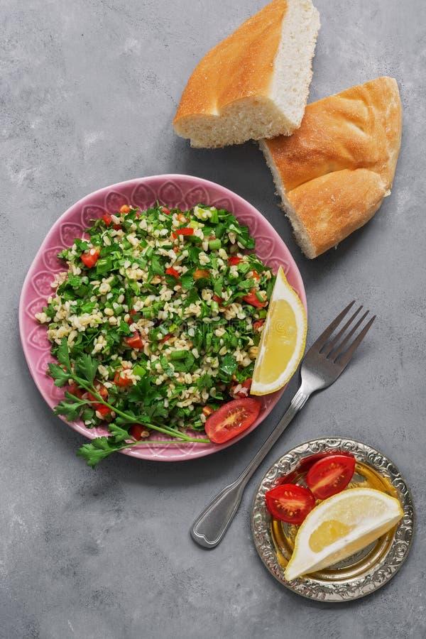 Bliskowschodnia lub Arabska naczynia tabbouleh sałatka z pita chlebem na szarym tle Odgórny widok obrazy royalty free