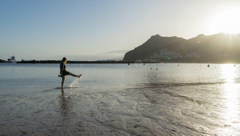 Bliss Teenager a balançar enquanto chuta a água com a perna, se divertindo no mar caminhando no pôr do sol Senhora risada e salpi imagem de stock