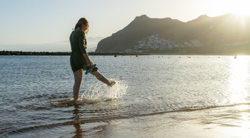 Bliss Teenager a balançar enquanto chuta a água com a perna, se divertindo no mar caminhando no pôr do sol Senhora risada e salpi fotografia de stock
