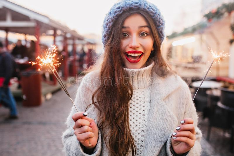 Blissful brown-haired woman with sincere smile enjoying christmas holidays and posing with sparkler. Charming girl in. Soft blue hat holding Bengal light on the stock photo