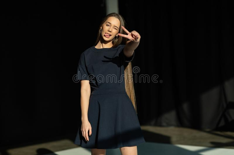 Blissful europian girl in black dress posin with peace sign. Shows her tongue royalty free stock image