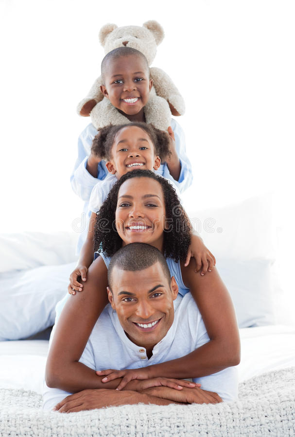 Blissful family having fun lying down on bed