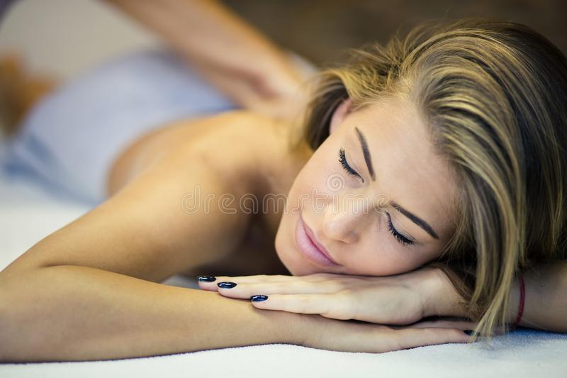 Blissful massage. Woman at a massage in spa center. Close up. Copy space. . Focus is on woman stock images