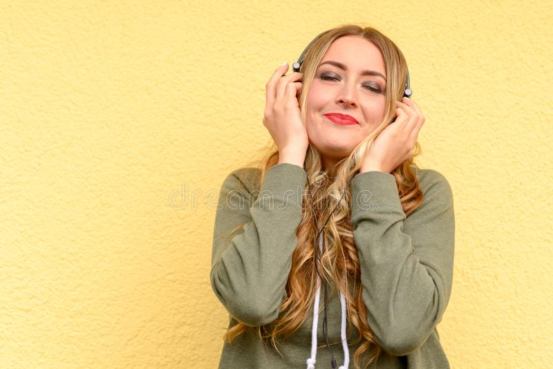 Blissful pretty blond woman listening to music. On stereo headphones with closed eyes and smile of pleasure over a yellow studio background stock photo