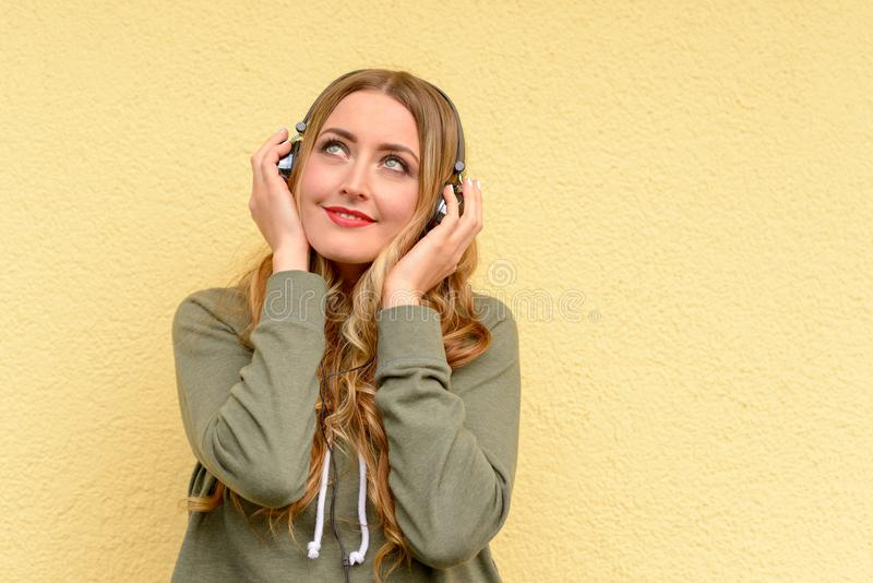 Blissful pretty blond woman listening to music. On stereo headphones with smile of pleasure over a yellow studio background stock photo