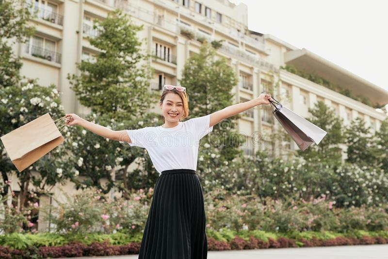 Blissful shopaholic woman dancing on the street with smile.  stock photo