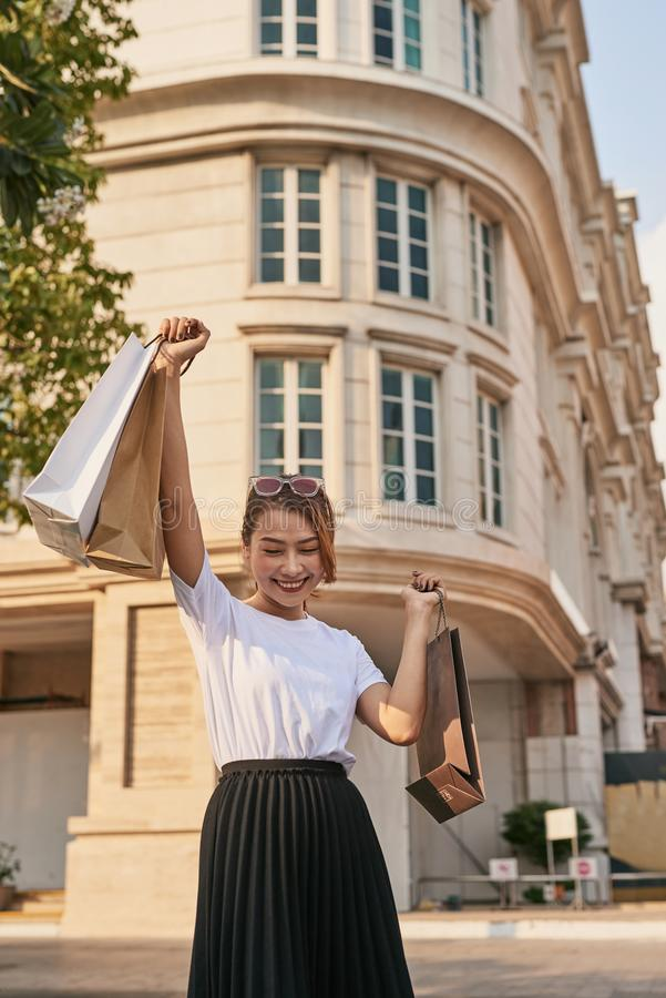 Blissful shopaholic woman dancing on the street with smile.  royalty free stock photos