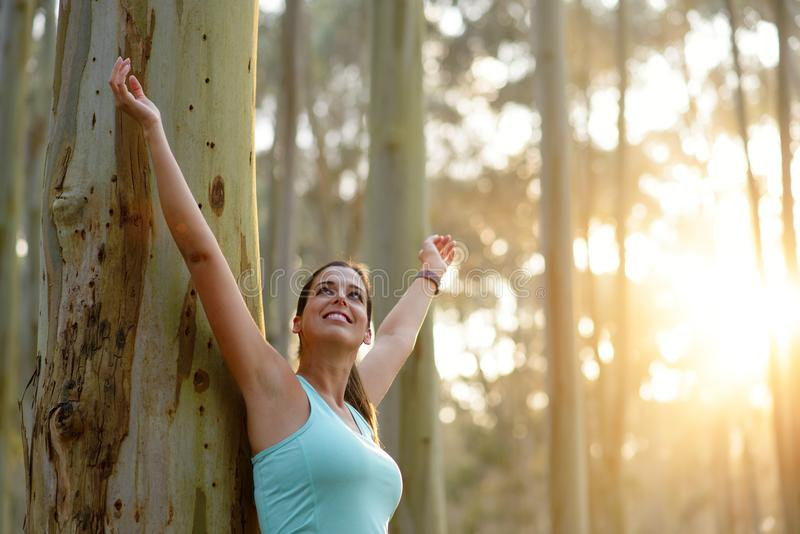 Blissful sporty woman enjoying freedom in nature. Outdoor healthy lifestyle concept royalty free stock photography