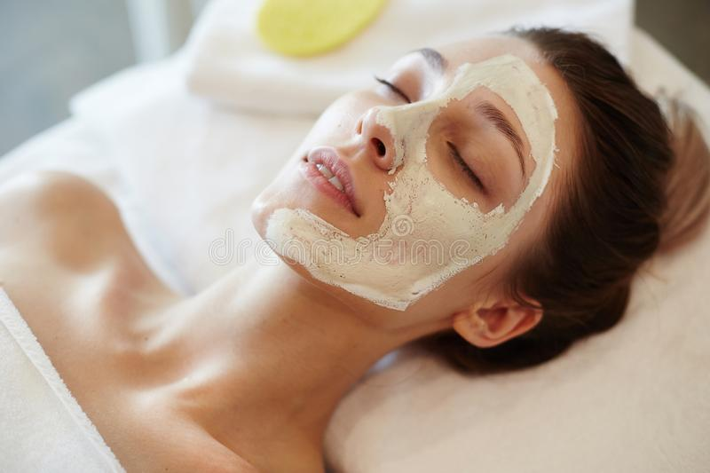 Blissful Woman Enjoying SPA. Closeup portrait of blissful young woman enjoying beauty treatments and face masks in SPA, lying on massage table with eyes closed royalty free stock images