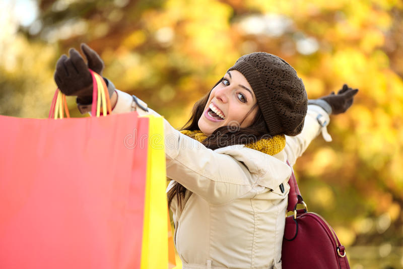 Blissful woman shopping and having fun in autumn. Blissful woman holding shopping bags and having fun buying in autumn rain. Successful female shopper outside in royalty free stock photography