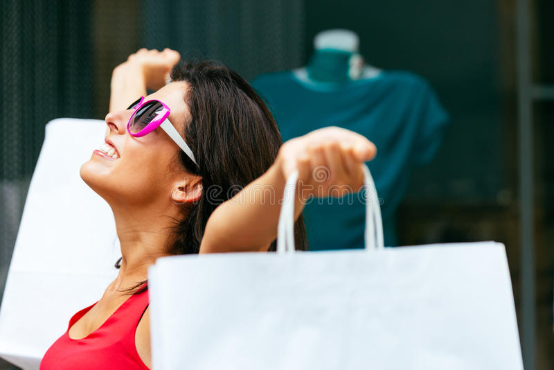 Blissful woman shopping in the sales. Blissful woman holding white shopping bags and enjoying the commercial store sales. Successful caucasian fashion brunette stock photo