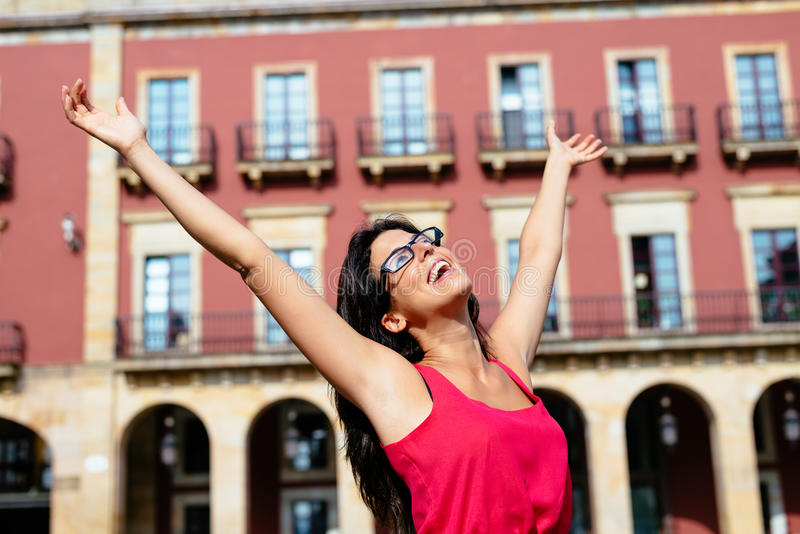 Blissful woman on vacation in spain. Blissful woman having fun on vacation in Gijon, Asturias, Spain. Successful european brunette girl raising arms on europe stock photography