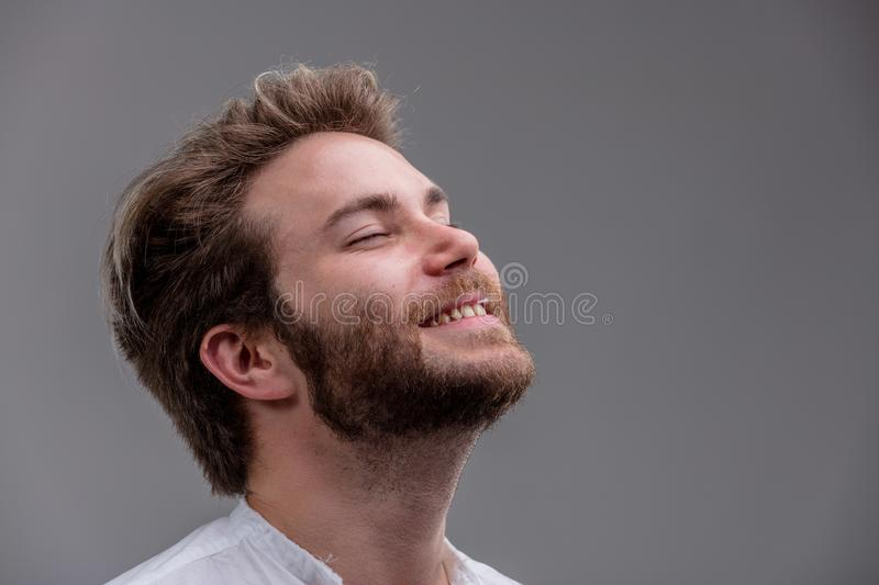 Blissful young man with his head tilted back. Blissful relaxed bearded young man with his head tilted back, closed eyes and a beaming smile isolated on grey with stock images