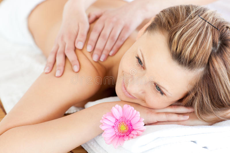 Blissful young woman enjoying a back massage. In a spa center royalty free stock photography