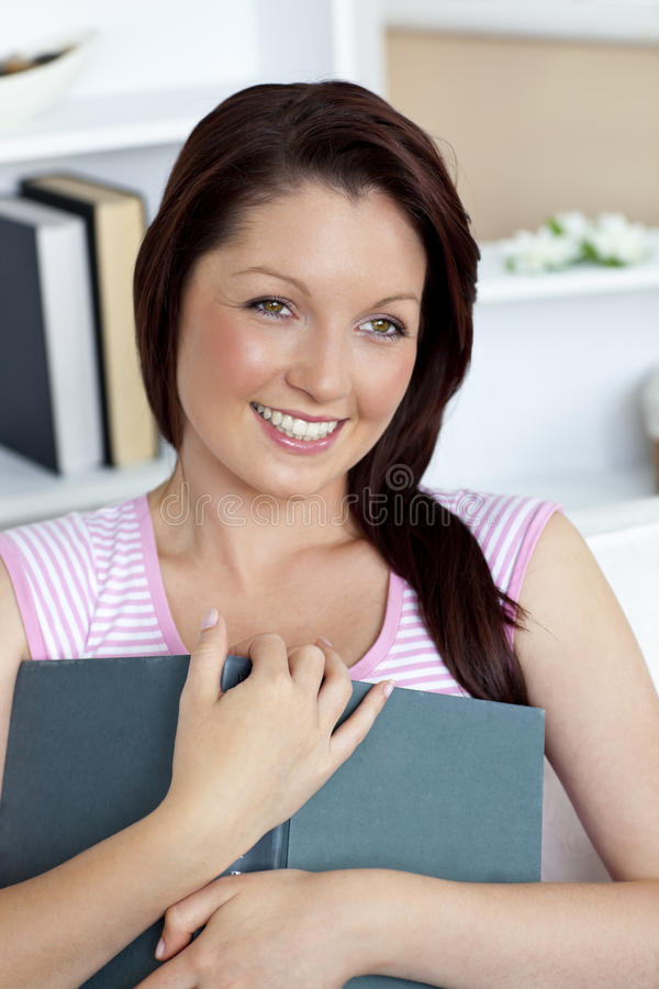 Blissful young woman holding a book on the couch. Blissful young woman holding a book sitting on the couch in the living room royalty free stock images