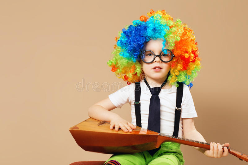 Blithesome children. Happy clown boy in large neon colored wig p. Laying the balalaika. Portrait of kid wearing clown wig and eyeglasses stock photography