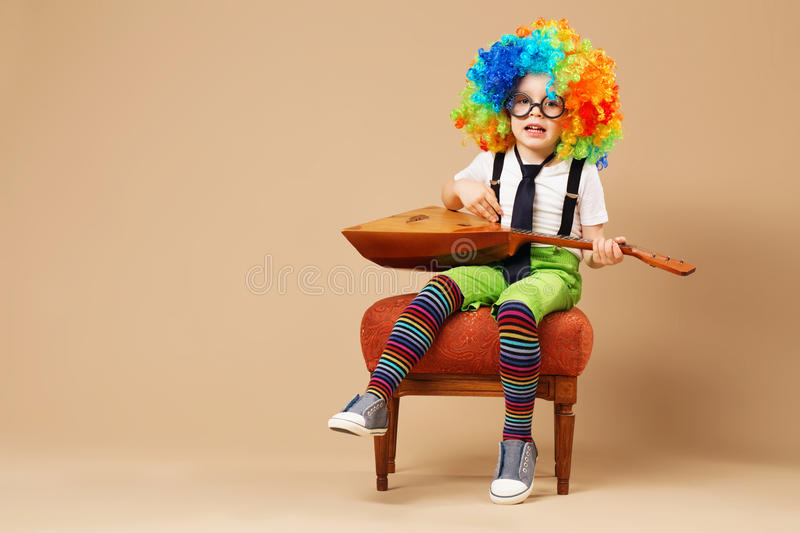 Blithesome children. Happy clown boy in large neon colored wig p. Laying the balalaika and singing. Portrait of kid wearing clown wig and eyeglasses royalty free stock image